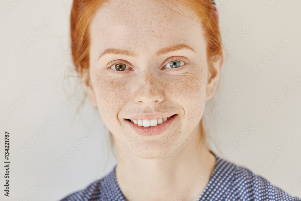 Fototapety, obrazy: Close up portrait of beautiful young redhead model with different colored eyes and healthy clean skin with freckles smiling joyfully, showing her white teeth, posing indoors. Heterochromia in human