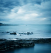 Peaceful Winter Seascape. Sea or Ocean with Dramatic Sky. Long Exposure. Calm Water and Moody Sky. Cold Mysterious Tranquility Concept. Blue Toned Photo with Copyspace.