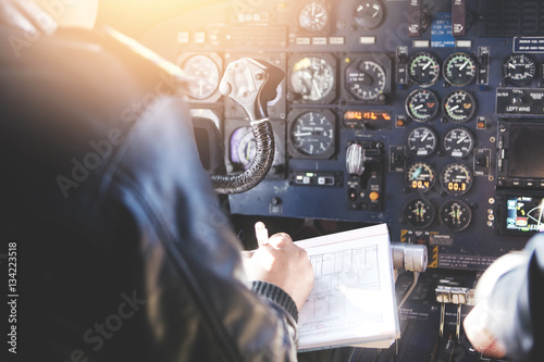 Fotografie, Obraz  Airplane crew sitting in cockpit with papers, filling in documention before performing flight