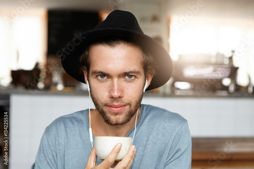 Attractive young male in black headwear holding mug, drinking tea or coffee and listening to music on his smart phone. Handsome hipster enjoying free time at cafe, using wireless internet connection