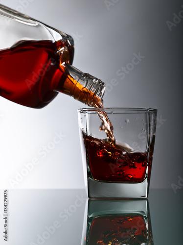 butelka-i-kieliszek-whisky-na-szklanym-stole