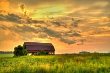 Wooden Barn Sunset. Rural Sunset With An Abandoned Barn Surrounded By Farm Fields.