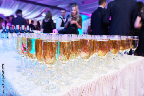 glasses with white sparkling wine in row at restaurant event Canvas Print