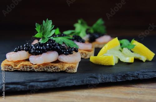 Foto op Plexiglas Voorgerecht закуска из креветок с черной икрой на хлебце с лимоном,