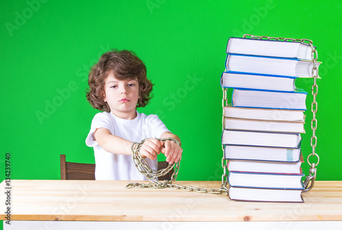 Offended little curly-headed boy in a white T-shirt stretched out his hands chained to the books Tapéta, Fotótapéta