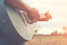 A Man Is Playing Guitar In Grass Field At Relax Day With Sun Light.