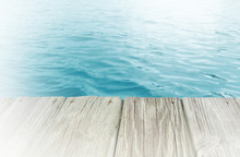 Background Image Of Inviting Azure Or Cyan Colored Water As Seen From The Edge Of A Wooden  Boardwalk. Sun Flare Bouncing Off Water In Distance. White Vignette Added.