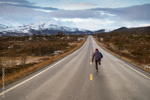 A man running down a road with mountains in the background. Poster