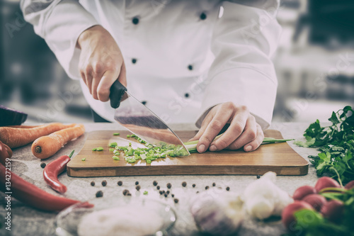 Photo sur Toile Cuisine The chef slicing vegetables.