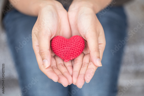 Fototapeta giving love. red heart in women her hand obraz
