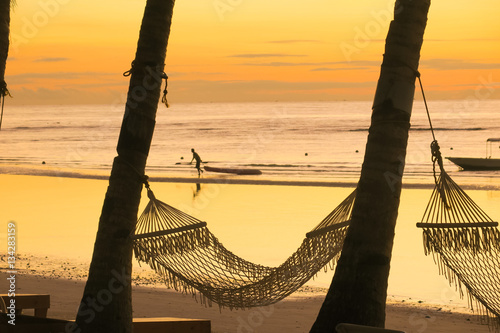 Photo  Hammocks lining a sunrise beach with kayaker in the distance