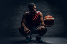 A Black Basketball Player Sits On A Floor And Holds Basket Ball.