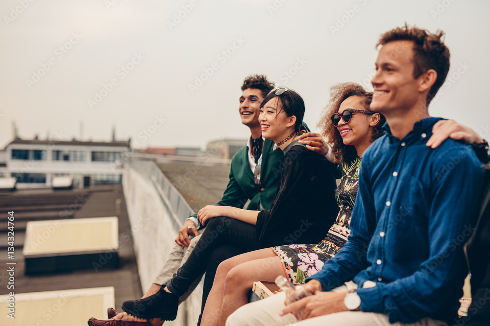 Fototapety, obrazy: Friends sitting together on rooftop
