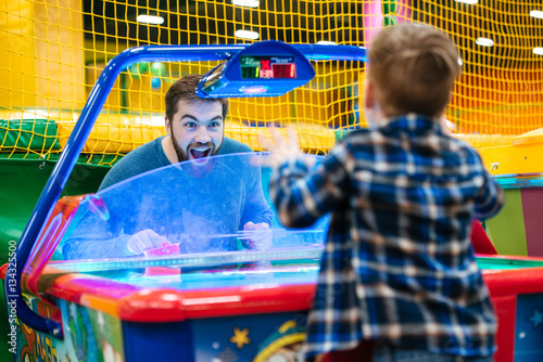 Staande foto Amusementspark Father and son playing air hockey game at amusement park