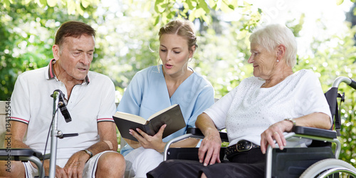 Láminas  Carer reads a book to the elderly persons