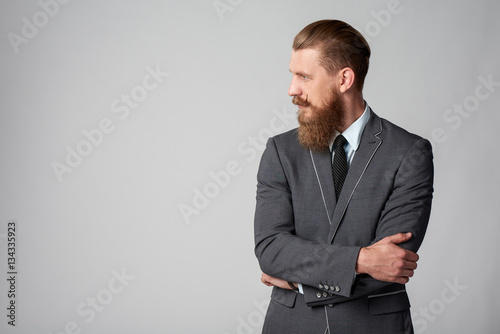 Valokuva  Confident stylish business man with beard and mustashes in suit standing with fo