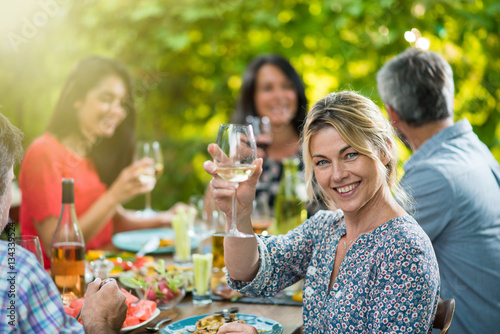 beautiful woman lunching with friends on a terrace table Poster