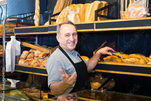 Leinwand Poster Portrait of  baker with fresh bread smiling in bakery