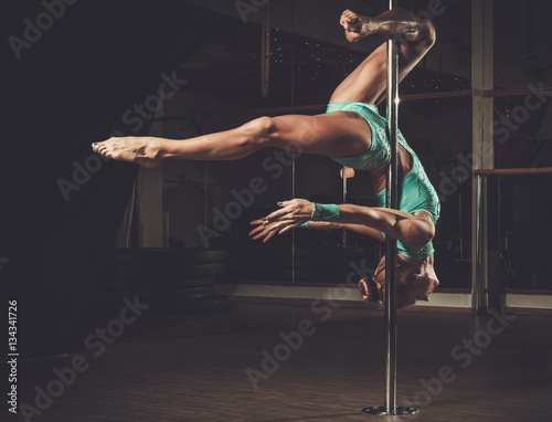 Beautiful woman performing pole dance on pole Wall mural