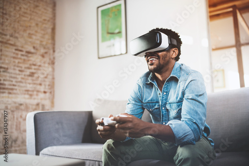 7ab74fa54915 Happy african man enjoying virtual reality glasses while relaxing on  sofa.Smiling young guy with VR headset playing video game at home.Blurred.