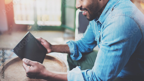 Fototapety, obrazy: Closeup view of young bearded African man using tablet while sitting on sofa at home.Concept people working with mobile gadget.Blurred background, flares,crop