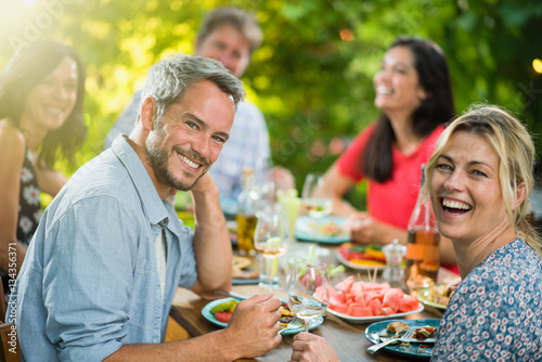 a group of friends gathered around a table on a terrace