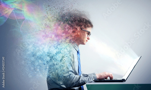 Office man in shirt and glasses sitting at a laptop