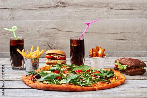 Junk food on wooden background. © margostock