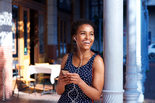 young black woman smiling outside with cellphone and earphones - 134357985