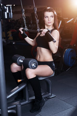 Fototapeta na wymiar Muscular brunette fitness girl doing exercises in the gym. Fitness girl lifting weights on a machine for bodybuilders.
