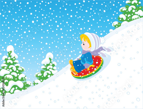 In de dag Regenboog Child on a snow tube sliding down the snow hill