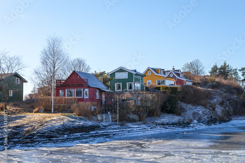 Staande foto Scandinavië Color wooden cabins on the island with frozen sea at the foreground. Scandinavian style