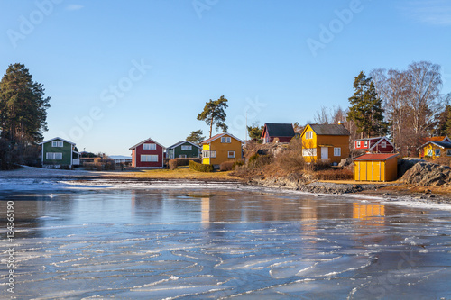 Staande foto Scandinavië Color wooden cabins on the island with frozen sea at the foreground. Scandinavian style. Sunny winter day