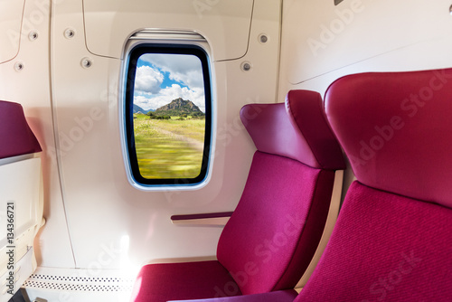 Poster Bordeaux Idillic country side with cloudy sky viewed from inside a modern train wagon