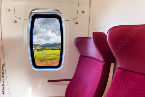 Idillic country side with cloudy sky viewed from inside a modern train wagon