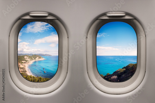Foto op Aluminium Vliegtuig Coast with clear blue sea and beach viewed from inside an airplane windows