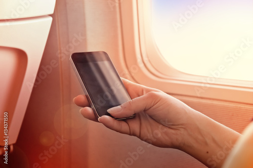 Fotografie, Obraz  Using mobile on a plane. Smartphone in woman hand