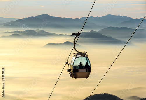 Spoed Foto op Canvas Gondolas Sight on the cable-way infrastructure over foggy valley. Ropeway and cablecar transport system for skiers