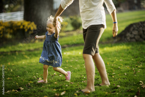 Happy young girl walking hand in hand with her mother.