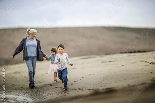 Grandmother walking on the beach with her grandchildren - 134382339
