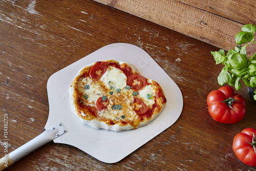 margherita pizza on shovel in classic pizzeria
