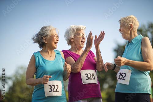 Three elderly friends have fun at an athletics event.
