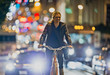 Smiling young woman riding her bicycle along a busy city road at night.
