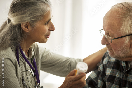 Female doctor speaking with an elderly male patient while holding a bottle of medication.