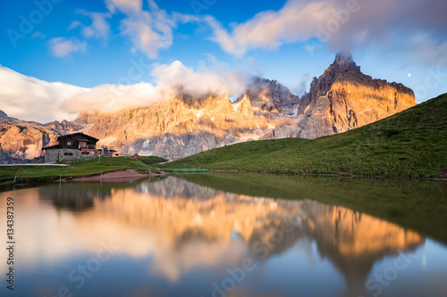 Poster Reflexion The Pale di San Martino peaks (Italian Dolomites) reflected in the water at sunset, with an alpine chalet on background.