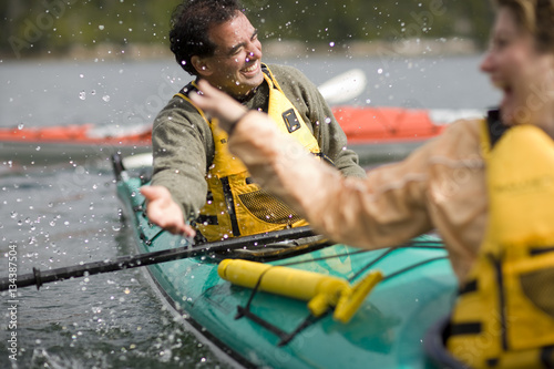 Happy mid-adult couple sitting in a kayak on a lake. Poster