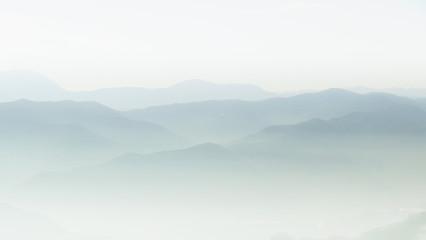 Fototapeta Mountain layer in morning sun ray and winter fog