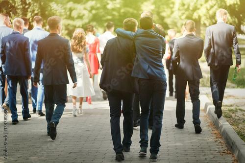 Fotografia, Obraz stylish confident man in suit having fun, group of people walkin
