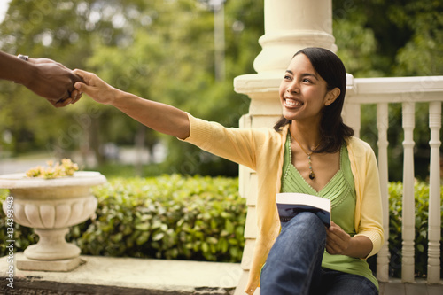 Young woman reaches up to take the hand of a man and smiles as she sits on a porch holding a book Poster
