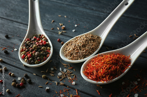 Foto auf AluDibond Gewürze 2 Assortment of spices in ceramic spoons on wooden background